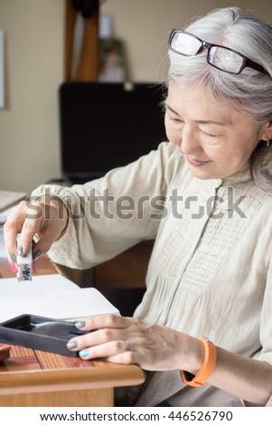 Asian senior woman artist using Japanese Suiteki Water Dropper and sudzuri ink stone. Focus on eyes. Art background - stock photo