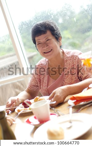 Asian senior woman enjoying her dining with family in a restaurant - stock photo