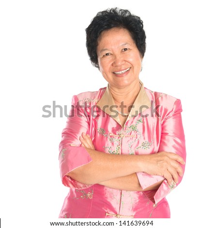 Asian senior woman. Happy smiling Asian grandparent standing isolated on white background. - stock photo