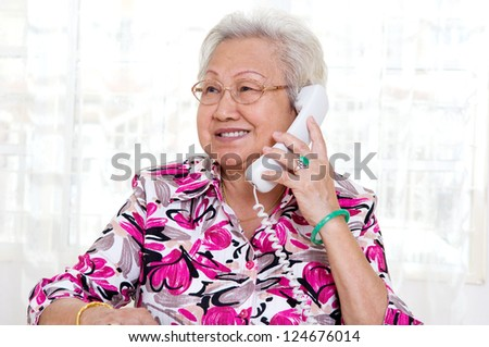 Asian senior woman in her 70s talking on the phone - stock photo