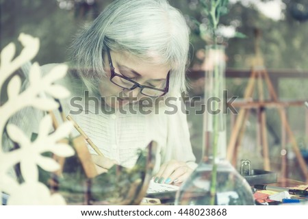 Asian senior woman painting at her home studio, view through window. Soft focus on eyes. Active old lady concept - stock photo