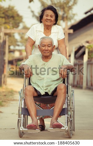 Asian senior woman pushing her disabled hasband on wheelchair - stock photo