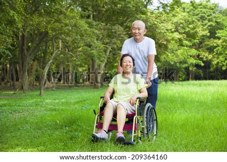 Asian senior woman sitting on a wheelchair with his husband - stock photo
