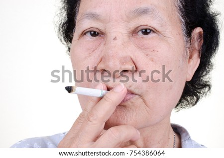 Asian Senior woman smoking cigarette
