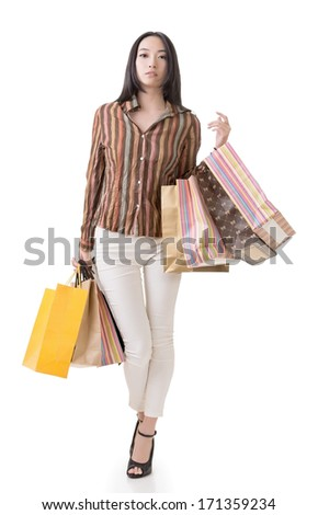 Asian shopping woman holding bags, full length portrait isolated on white.