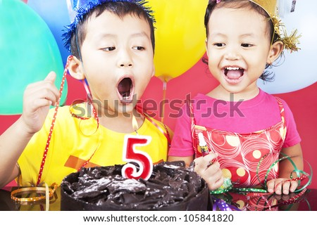 Asian sibling celebrating fifth birthday, shot in studio at birthday party - stock photo