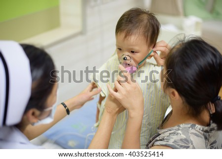 Asian sick boy wearing oxygen mask by nurse and mom - stock photo