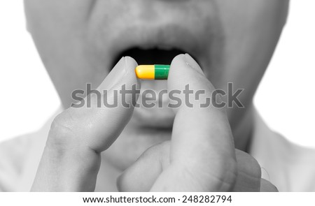 asian sick man / male patient open mouth for eating yellow / green drug capsule , isolated on white - stock photo