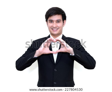 Asian smiling businessman with heart made from hands. - stock photo