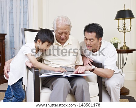 asian son, father and grandfather reading a book together. - stock photo