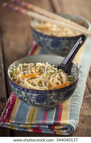 Asian soup with noodles in a decorated bowl on a wooden table