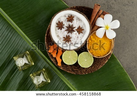 Asian spa setting with coconut, turmeric, lime, cinnamon, anise and oil in wooden tray on banana leaf - stock photo