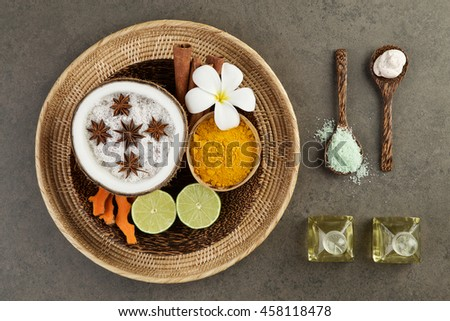 Asian spa setting with coconut, turmeric, lime, cinnamon, anise, scrub, salt sea and oil in wooden tray - stock photo