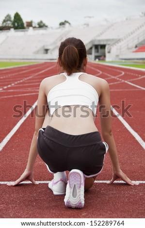 Asian sport girl exercise in public national stadium. - stock photo