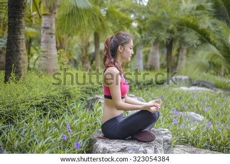 Asian sport girl yoga in the park