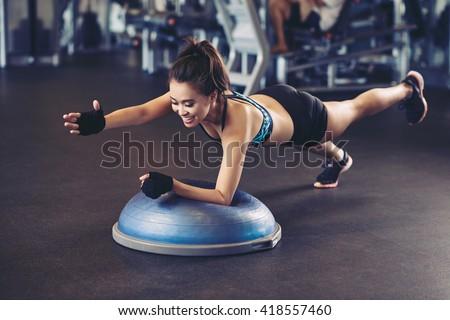 Asian sportswoman performing exercise on bosu ball - stock photo