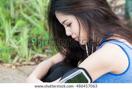 Asian sporty woman listening to music in earphones from smart phone, player smart phone armband.
