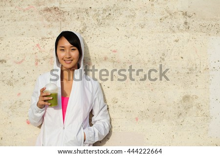 Asian sporty woman taking fitness workout rest for drinking healthy fitness detox smoothie. Happy female athlete on training break. - stock photo