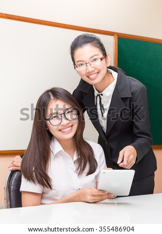 Asian student and teacher in classroom - stock photo
