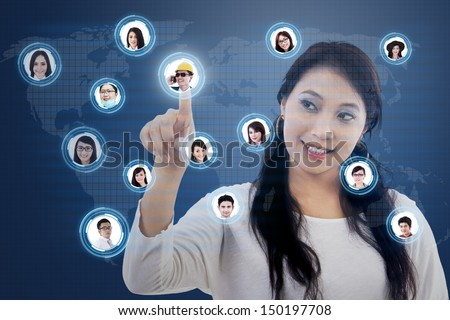 Asian student clicking on the social networking map with digital world map - stock photo