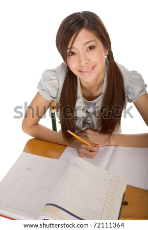 Asian student girl sitting by the desk and studying huge math book, preparing to test - stock photo
