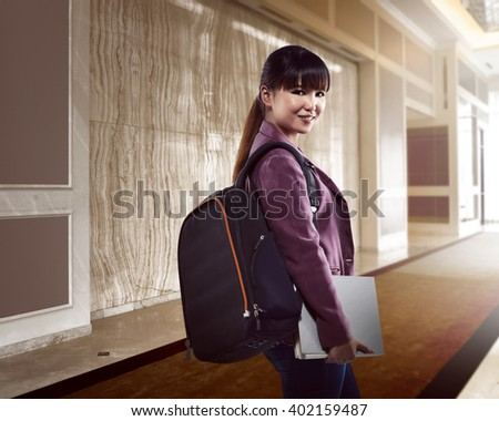 Asian student holding book inside college building