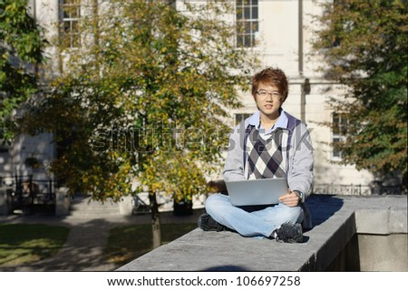 Asian student outdoors with laptop - stock photo