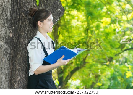 Asian student reading blue book, against green of summer park. - stock photo