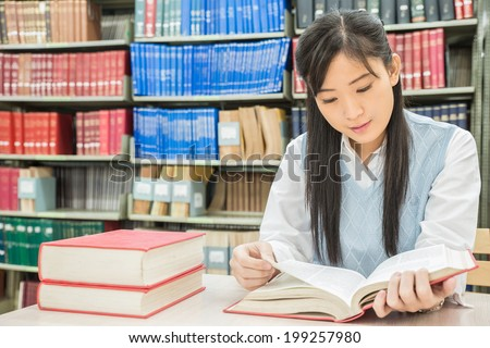 Asian student reading book in library at university - stock photo