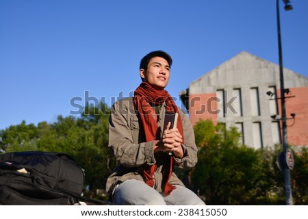 Asian student sitting holding book at campus - stock photo