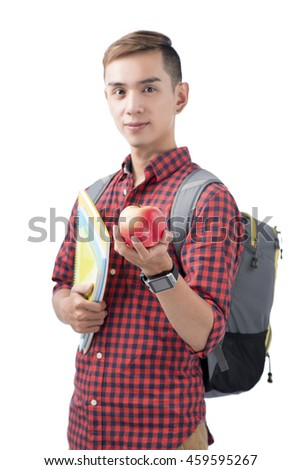 Asian student standing on white with books and apple. Back to school concept.
