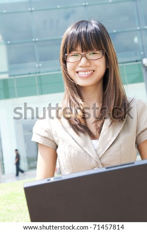 Asian student using laptop outside modern building - stock photo