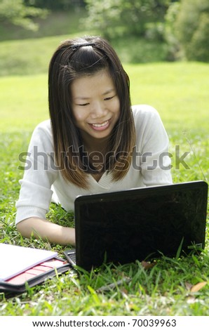 Asian Student Using Laptop Outside School Campus - stock photo