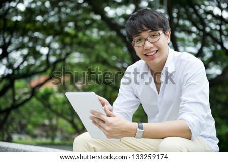 Asian student using tablet - stock photo
