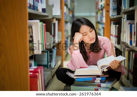 Asian student was reading in the library and Understanding Read books - stock photo