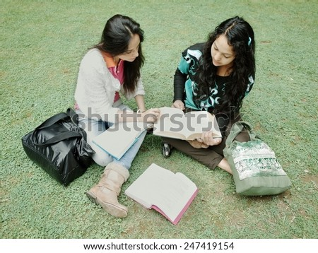 Asian students sitting on grass and studying. - stock photo