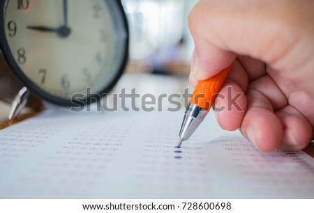 Asian Students taking optical form of standardized exams near Alarm clock with hand holding yellow pen for final examination in secondary school, college university classroom, Education concept