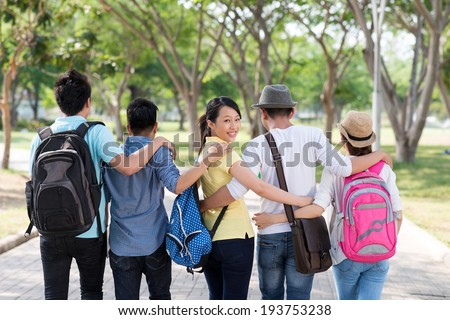 Asian students walking in the park together, view from the back - stock photo