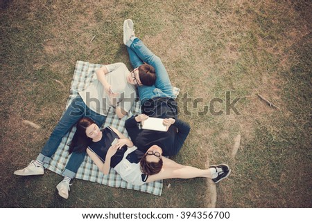 Asian students with mobile devices resting in the park, view from above - stock photo