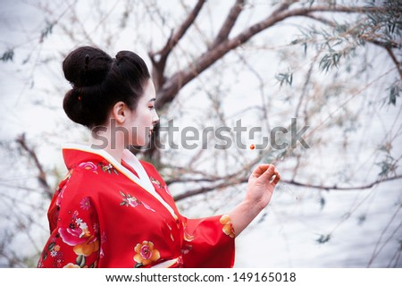 Asian style portrait of a woman in red kimono with a little red flower - stock photo
