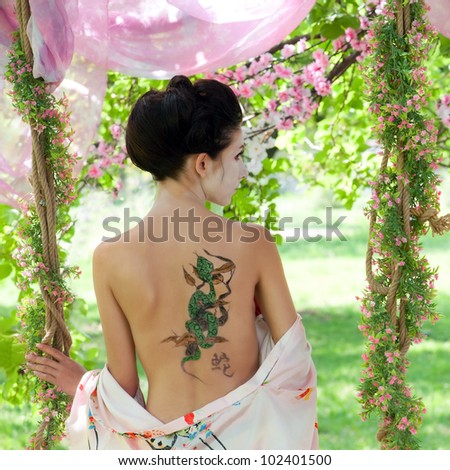 Asian style portrait of young woman with snake tattoo on her back - stock photo