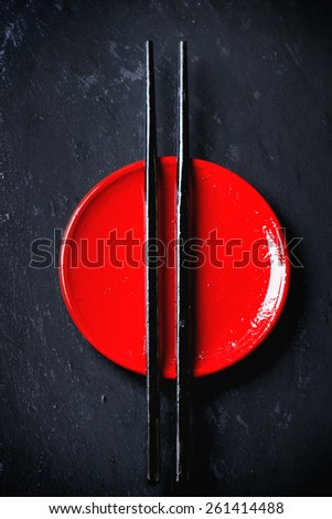 Asian style red plate and black chopsticks over dark background. Top view - stock photo