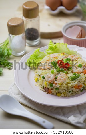 Asian style seafood fried rice with egg on wooden kitchen counter top.  - stock photo
