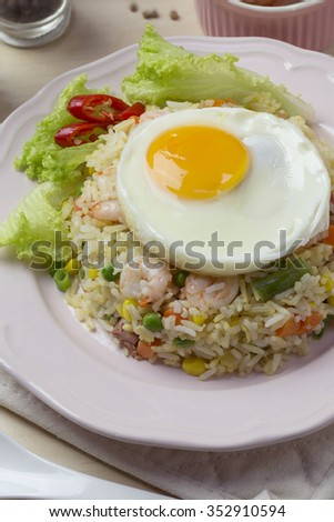 Asian style seafood fried rice with sunny side up egg on wooden kitchen counter top. Closeup. - stock photo