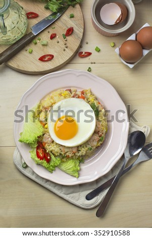 Asian style seafood fried rice with sunny side up egg on woody kitchen counter top.  - stock photo