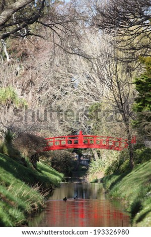 Asian styled red arched bridge crossing a stream in the Oamaru Botanical gardens, New Zealand  - stock photo
