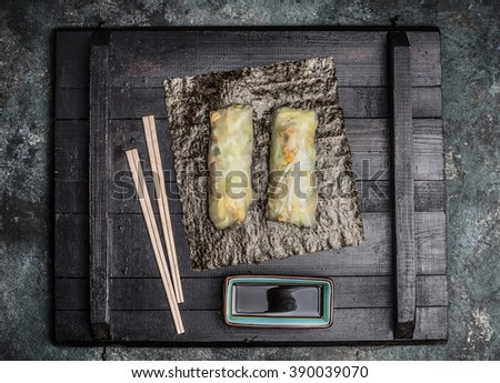 Asian summer rolls with chopsticks and soy sauce on dark rustic background, top view - stock photo