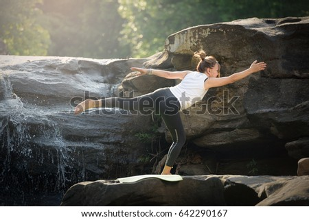 Asian tall women wear white robes, do yoga on rocks in forests, and mountains with beautiful waterfalls. Health and Fitness Concept.