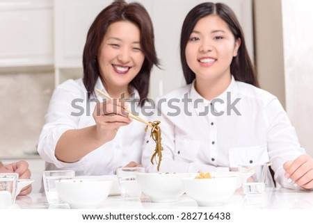 Asian tasty food. Asian mommy and daughter at home together having dinner - stock photo