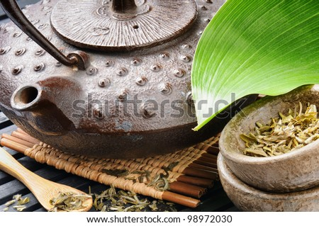 Asian tea set with green leaf on wooden mat - stock photo